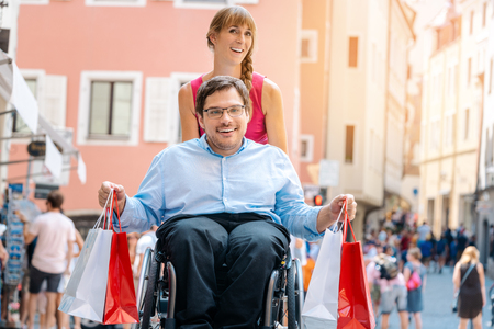 Photo for Man in wheelchair being pushed by his friend on a shopping trip with bags - Royalty Free Image