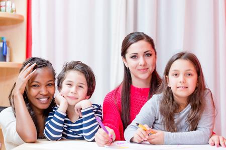 Photo pour Portrait of tutor sitting with children teaching them drawing - image libre de droit