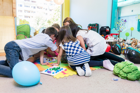 Photo pour Group of pre-school children surrounding their skilled teacher during an educational activity in the classroom of a modern kindergarten - image libre de droit