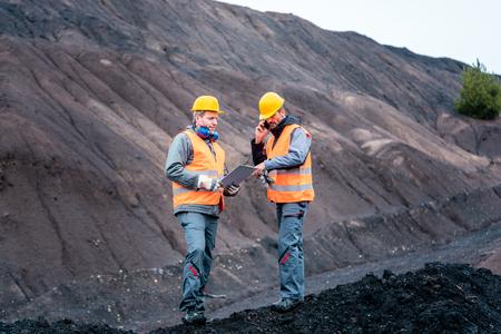 Foto de Workers standing in open-cast mining operation pit - Imagen libre de derechos
