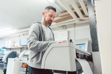 Man preparing large format printer for a banner print job on vinyl