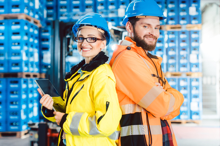 Photo pour Worker woman and man in warehouse posting for the camera - image libre de droit