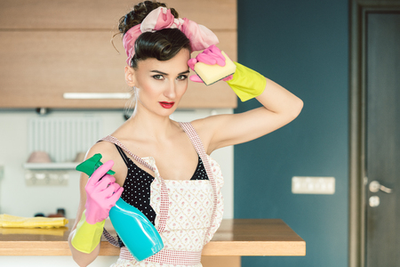 Photo pour Housewife woman in retro outfit attempting to clean the kitchen wiping sweat from forehead - image libre de droit