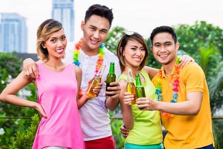 Photo pour Portrait of a happy young friends celebrating in park - image libre de droit