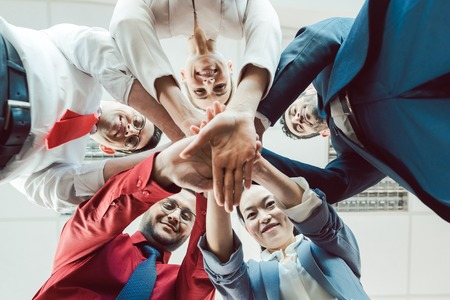 Photo pour Team of diverse business people stacking their hands together, seen from below - image libre de droit