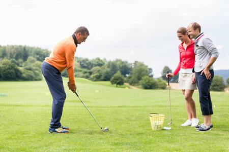 Photo pour Smiling couple looking at male coacher taking a shot on golf course - image libre de droit