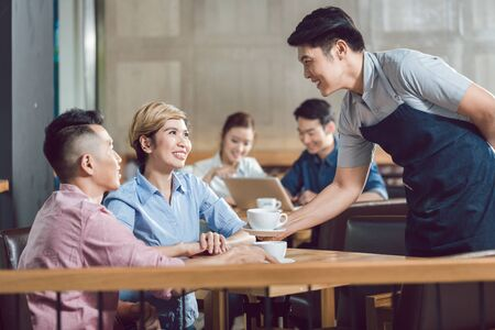 Photo pour Young smiling couple being served with coffee at table in the cafe - image libre de droit