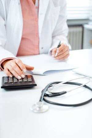 Photo pour Closeup of doctor using calculator writing bills and doing bookkeeping - image libre de droit