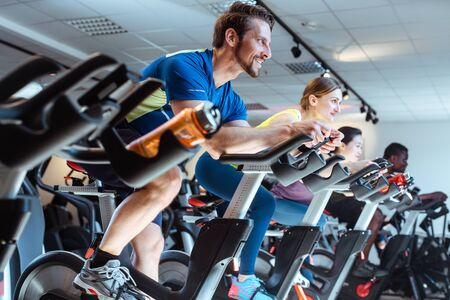Photo pour Caucasian man and friends on fitness bike in gym during workout - image libre de droit