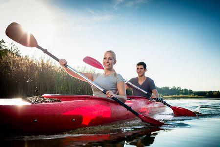 Photo pour Happy young couple paddling in kayak over sunlight - image libre de droit
