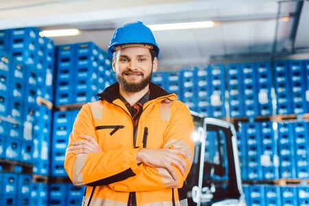 Photo pour Worker in a forwarding company with his forklift looking into the camera - image libre de droit