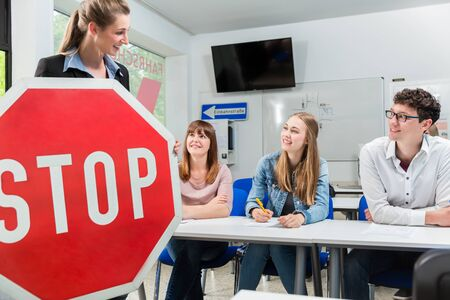 Photo pour Driving instructor holding theoretical part of driving lessons with stop sign in her hand - image libre de droit
