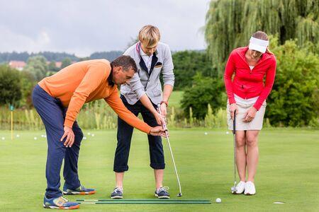 Foto de Mature male golf trainer teaching the couple to play golf on golf course - Imagen libre de derechos
