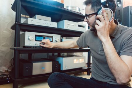 Photo pour Man turning up the volume on home Hi-Fi stereo for louder music - image libre de droit