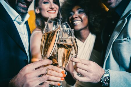 Photo pour Men and women celebrating birthday or new years party while clinking glasses with sparkling wine - image libre de droit
