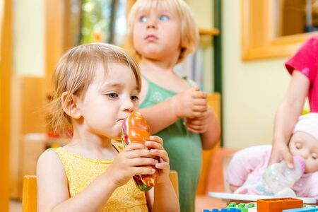 Photo pour Children eating some food in play school biting in sandwich - image libre de droit