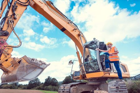 Photo pour Construction worker on excavator planning the work to be done on the site - image libre de droit