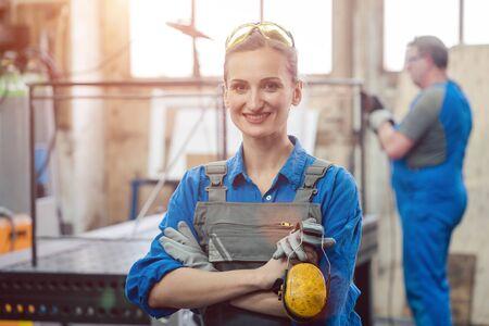 Photo pour Workers in a metal workshop, man and woman - image libre de droit
