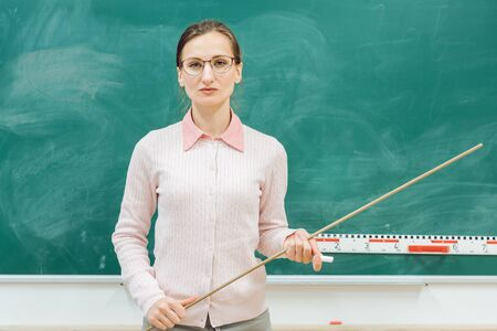 Photo pour strict teacher standing in front of blackboard in class with a pointer in hand - image libre de droit