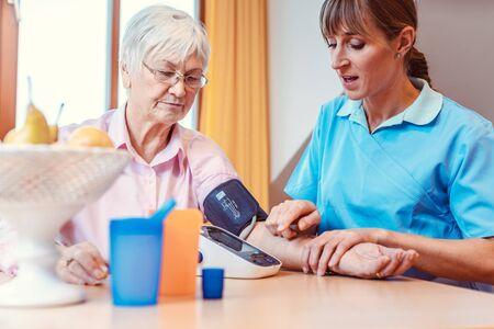 Nurse measuring blood pressure on senior woman, a medical test