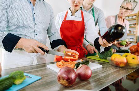 Foto de Man in training kitchen cutting vegetables under watchful eye of competent dietician - Imagen libre de derechos