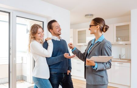 Photo pour Cheerful realtor giving house key to the buyers or tenants - image libre de droit
