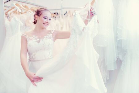 Photo for Young woman shopping in wedding shop for a dress to wear as a bride - Royalty Free Image