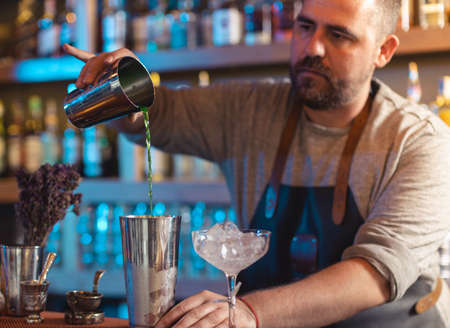 Photo pour Barman gently pouring beer into shaker on bar counter - image libre de droit