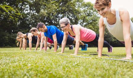 Foto de Fitness group practising push-ups in park - Imagen libre de derechos