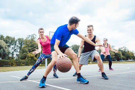 Photo pour Basketball players playing at outdoors court - image libre de droit