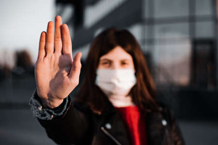 Young girl shows hand sign stop no to coronavirus epidemic pandemia originated at China. Covid-19 virus, nCov2019. Dramatic portrait of a girl is against virus and illness quarantineの素材 [FY310151569863]