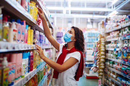 Foto für Young woman picks up the disinfecting and cleaning scour at a supermarket wearing a medical sterile mask during the coronavirus pandemic quarantine. Healthcare and home sanitizing concept - Lizenzfreies Bild
