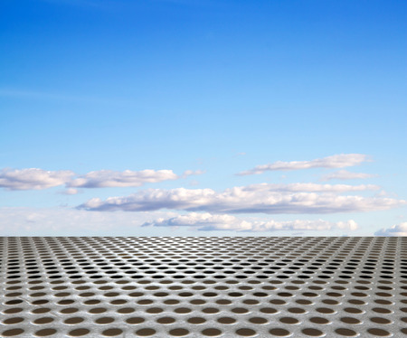 silver metal floor with round hole on the background of blue sky