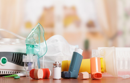 Photo pour Compressor and ultrasonic nebulizers, aerochamber, inhaler, thermometer and medicines to treat asthma on abstract pink background. - image libre de droit