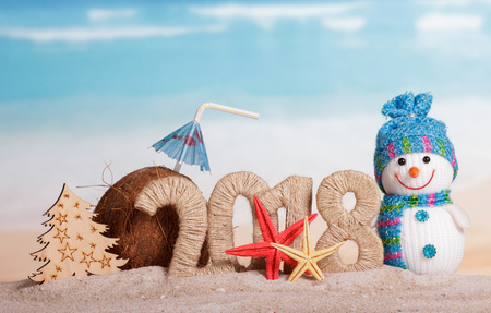 Photo pour New Year inscription 2018, a snowman, a Christmas tree, a coconut with a straw and umbrella, starfish on the sand. - image libre de droit