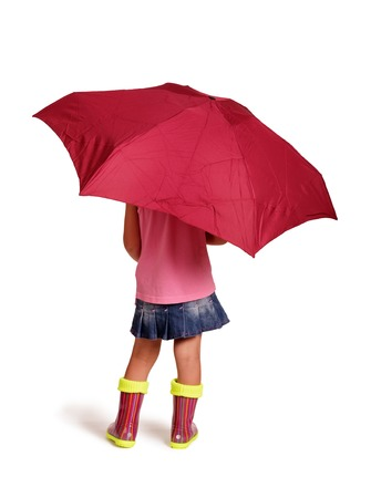 Little girl in rubber boots is standing under an umbrella, isolated on white backgroundの写真素材