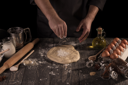 Hand of chef kneading dough, lot of the ingredients on table, isolated on black