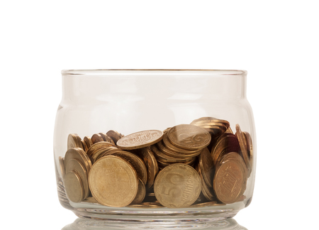Bunch of coins of different denominations in glass jar isolated on white