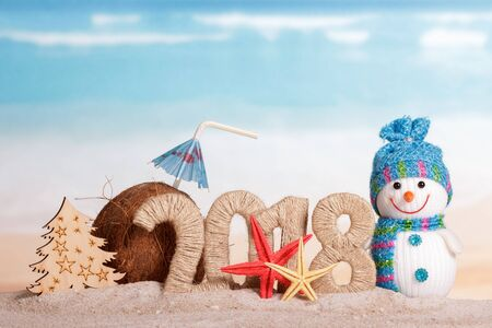 Photo pour New Year inscription 2018, coconut with drinking straw and umbrella, the snowman and the Christmas tree, starfish on the sand. - image libre de droit