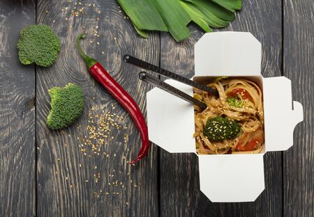 Hot fast food in box-wok, broccoli and chili pepper on dark wooden surfaceの素材 [FY310142039388]