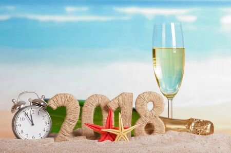 Photo pour New Year inscription 2018, a bottle and a glass of champagne, clock and starfish on the sand. - image libre de droit