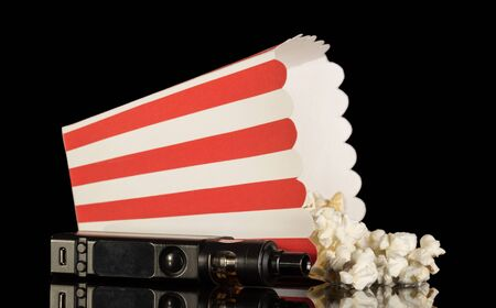 Photo pour Popcorn fell out of the striped box next to electronic cigarette isolated on black background - image libre de droit