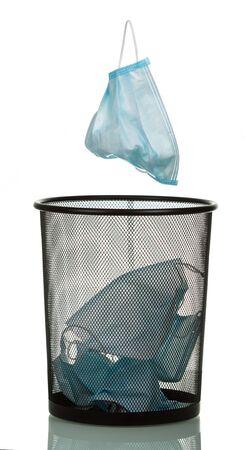 Foto de Another medical mask flies into the bin, isolated on white background - Imagen libre de derechos