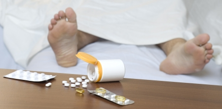 Different pills on the table. Person sleeping in the background. Impalanced diagonal composition