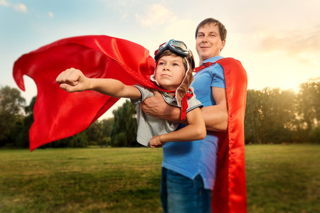 Photo for Father and son playing in superhero costumes in the park on nature. A happy family. Father's Day. - Royalty Free Image