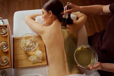 Photo for Young woman is put on a mask on her back in  spa salon. - Royalty Free Image