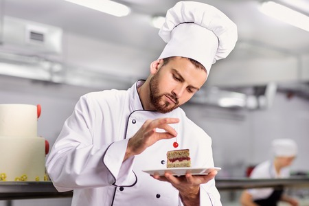 Foto per The confectioner is preparing a cake in the kitchen of the pastry shop. - Immagine Royalty Free