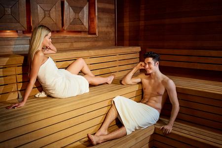 Foto de Couple in towels resting in the sauna. Man and woman in a spa salon. - Imagen libre de derechos