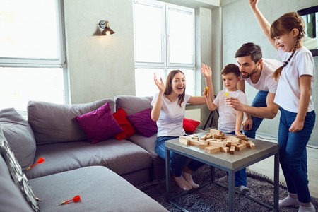 Foto de Happy family playing board games at home. Mother, father and children play together. - Imagen libre de derechos