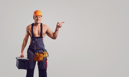 Foto de Sexy repairman in helmet smiling at the special clothes with a working tool on a gray background. - Imagen libre de derechos